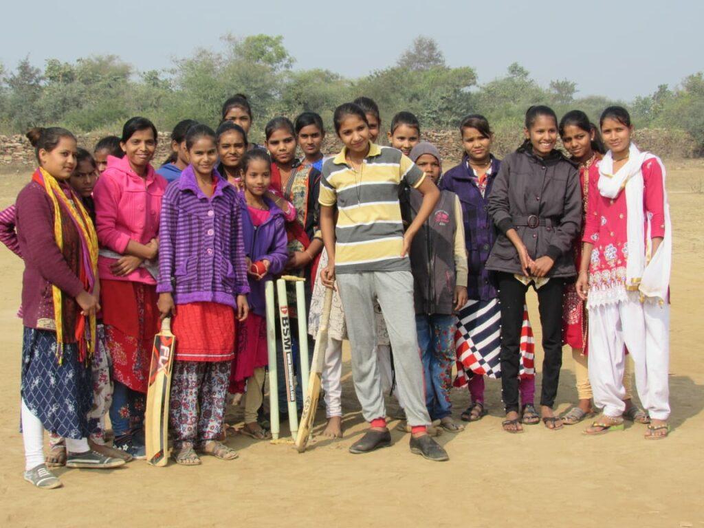 A girls' cricket team posing for the camera, in Budhpura, Rajasthan, India.