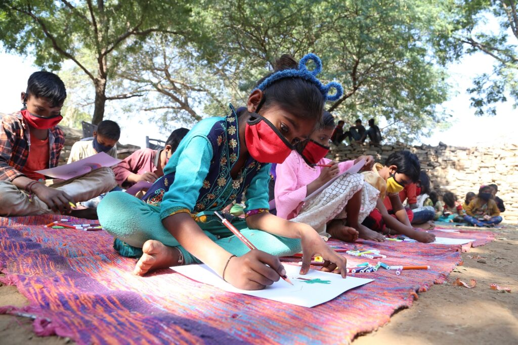 A class of young children sitting on the ground in open air class, wearing masks because of Covid virus, Rajasthan, India,