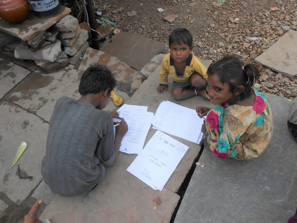 Group of 3 children of different ages, sitting on stone slabs, with worksheets spread around. in Budhpura, Rajasthan, India. They're not in school because of Covid restrictions.