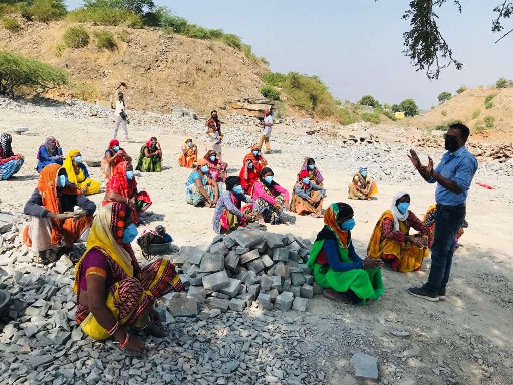 Women sitting spaced apart in rows on dusty ground receiving instructions.