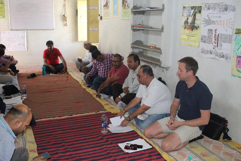 No Child Left Behind meeting in Budhpura. Men sitting on floor around edge of room.