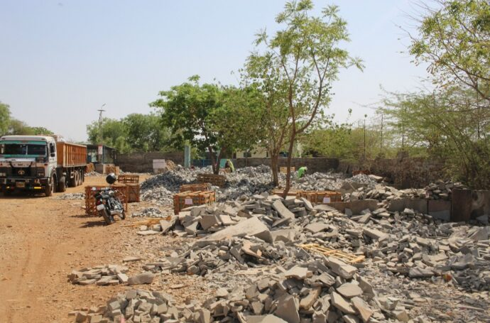 Indian cobble yard. Piles of stone and women picking through it